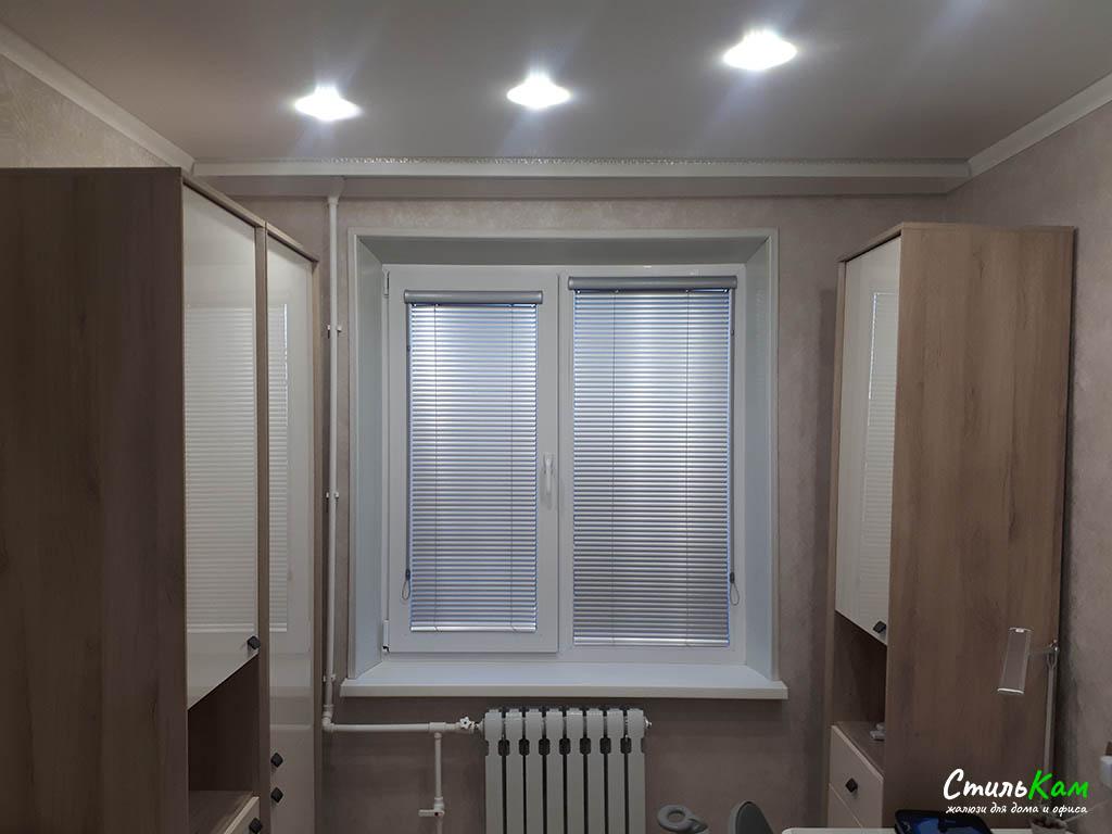 кассетные алюминиевые жалюзи на окне в комнате